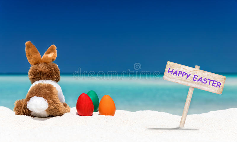 Il coniglietto, le uova di Pasqua e Pasqua felice firmano su una spiaggia immagine stock libera da diritti