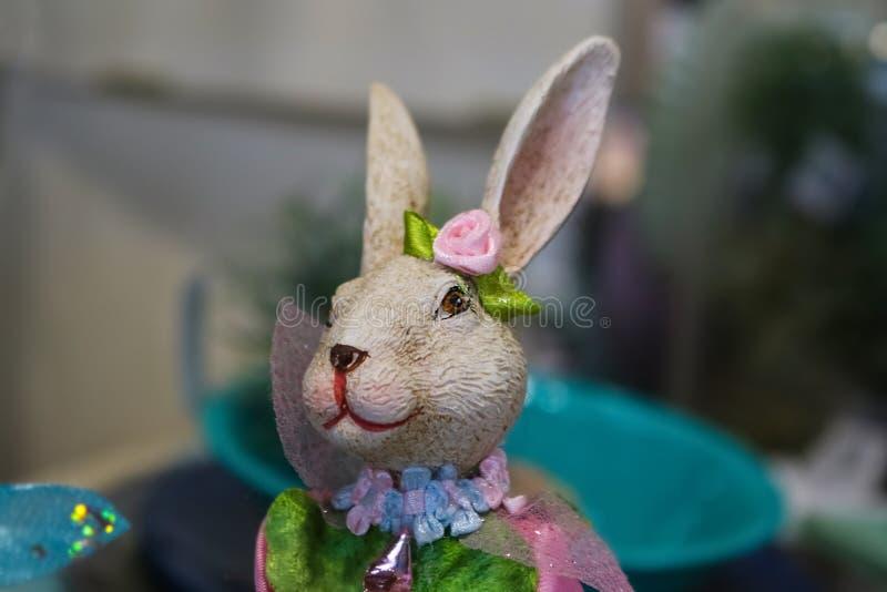 Il coniglio di coniglietto grazioso della ragazza interamente ha decorato per la molla con i fiori ed i nastri contro il fondo de immagine stock libera da diritti