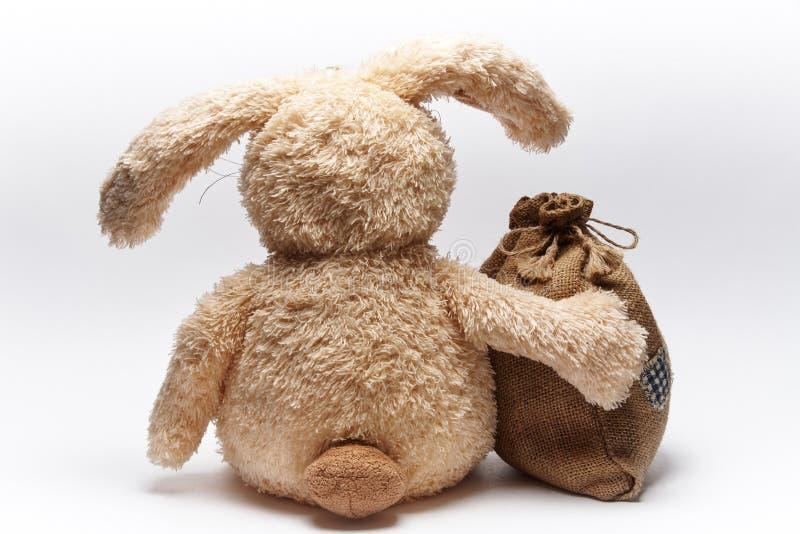 Il coniglio molle del giocattolo si siede con una borsa fotografia stock libera da diritti