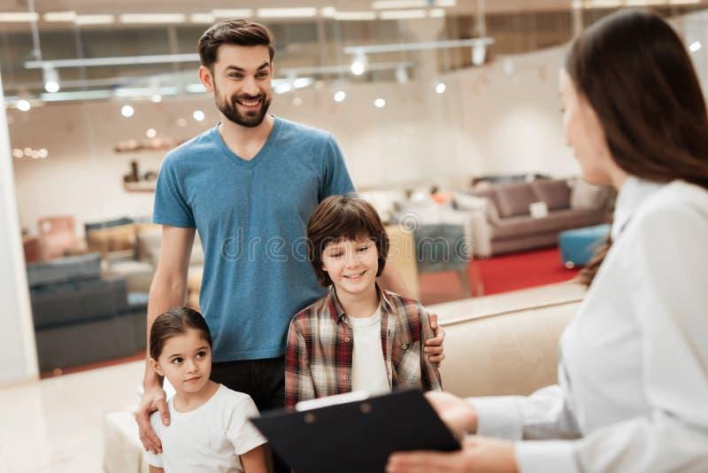 Il consulente in materia della donna bianca dimostra il materasso ortopedico al giovane padre con i bambini in negozio di mobili immagine stock libera da diritti