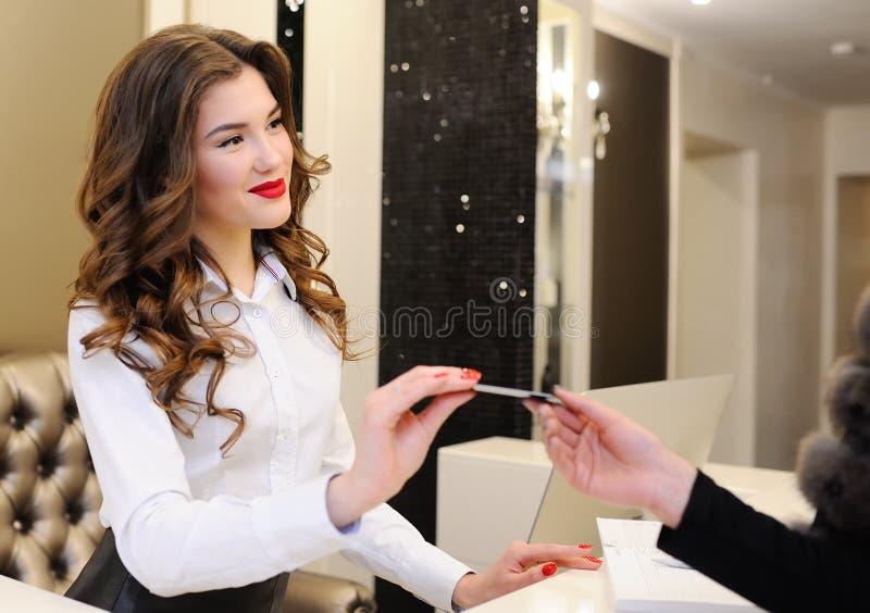 Il consulente in materia della ragazza dà una carta di sconto al cliente fotografia stock libera da diritti