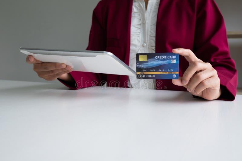 Il consumatore di donna di affari che tengono la carta di credito e la compressa per acquisto ed il pagamento online fanno un acq fotografie stock libere da diritti