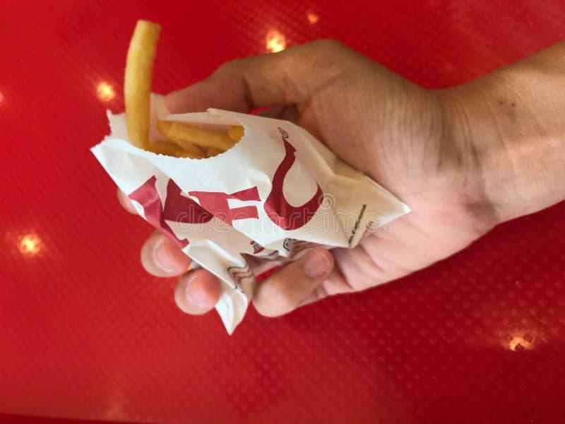 Il consumatore nowaday è con le patate fritte che serviscono a KFC immagine stock libera da diritti
