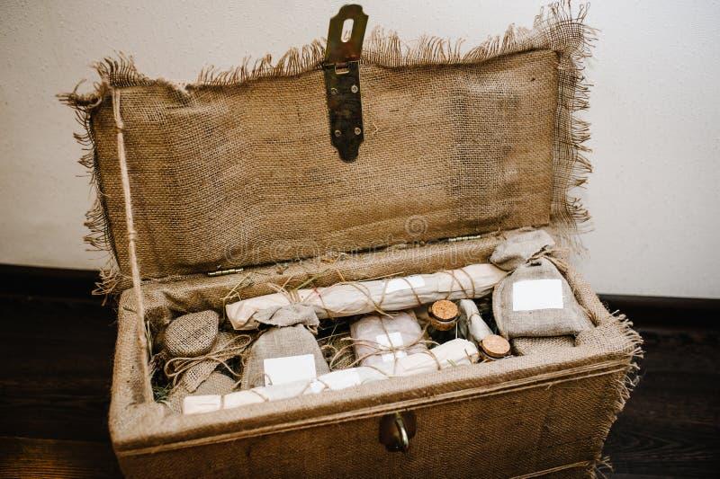 Il contenitore di regalo aperto è imballato in tela di sacco, con i prodotti domestici in involucri Vista superiore sorpresa vita immagini stock libere da diritti