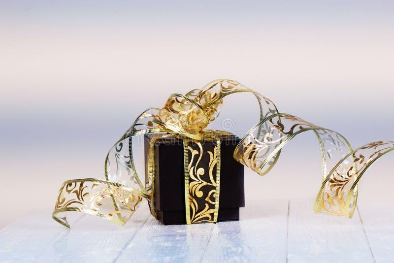 Il contenitore di regalo con il nastro dorato su bianco ha dipinto il fondo di legno C fotografia stock libera da diritti