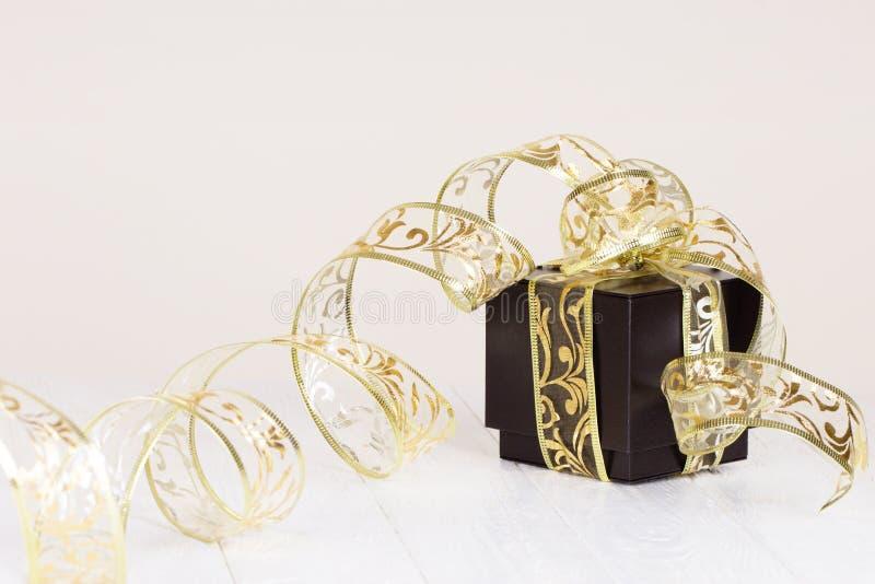 Il contenitore di regalo con il nastro dorato su bianco ha dipinto il fondo di legno C immagine stock