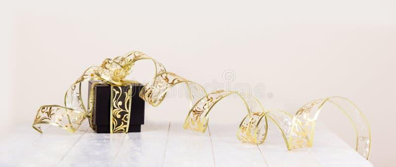 Il contenitore di regalo con il nastro dorato su bianco ha dipinto il fondo di legno C immagini stock libere da diritti