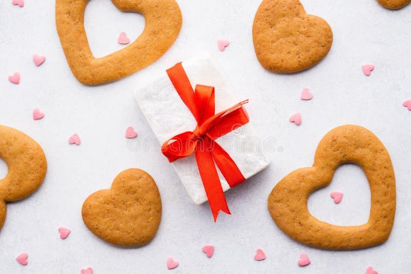 Il contenitore di regalo con il nastro rosso, cuore ha modellato i biscotti e la caramella fotografia stock libera da diritti