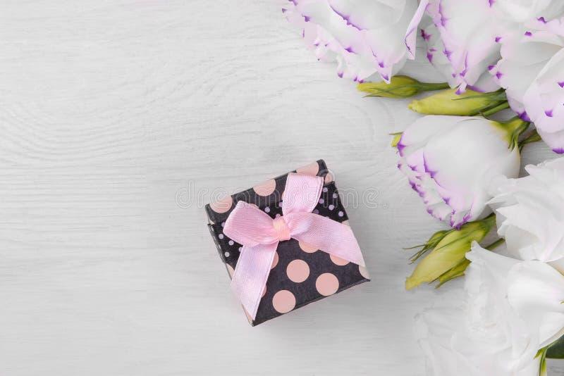 Il contenitore di regalo con un arco rosa e un bello eustoma bianco fiorisce su una vista superiore del fondo di legno bianco immagini stock