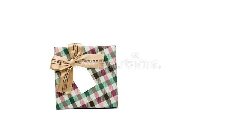 Il contenitore di regalo del modello del plaid con l'arco beige del nastro e la cartolina d'auguri in bianco isolati su fondo bia immagini stock