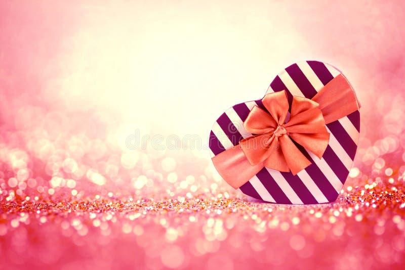 Il contenitore di regalo di forme del cuore di rosso sul backgrou leggero astratto di scintillio immagine stock
