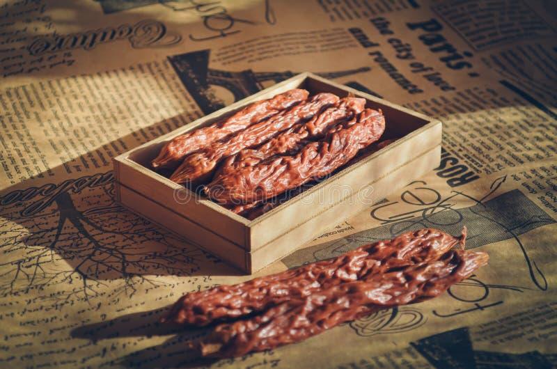 Il contenitore di regalo di legno ha fumato le salsiccie piccanti Salsiccie di caccia Fondo e fuoco molli caldi fotografie stock libere da diritti