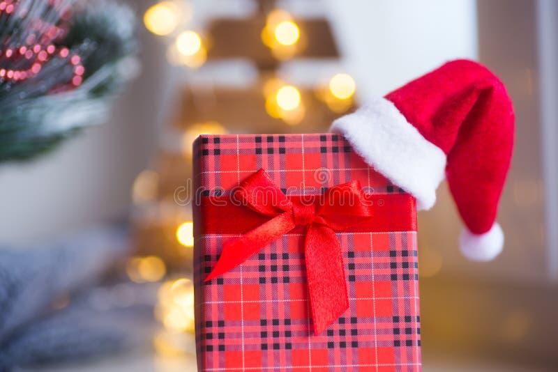 Il contenitore di regalo a quadretti rosso del primo piano con l'arco in piccolo cappello di Santa del giocattolo con la ghirland fotografia stock libera da diritti
