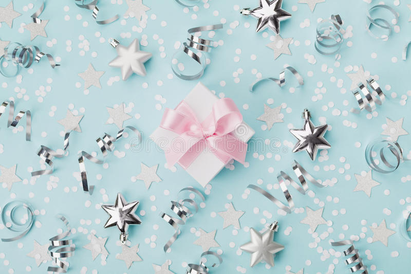 Il contenitore di regalo sul fondo blu di natale ha decorato la vista superiore delle stelle dell'argento e dei coriandoli Dispos fotografia stock libera da diritti