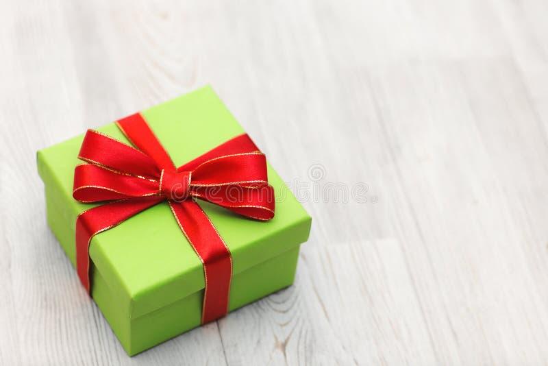 Il contenitore di regalo verde con l'arco rosso del nastro ha messo su un fondo di legno fotografia stock libera da diritti