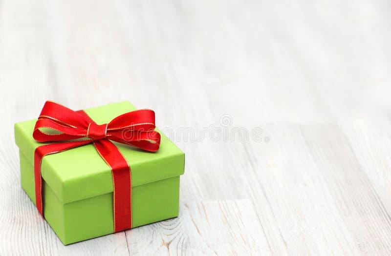 Il contenitore di regalo verde di Natale con l'arco rosso del nastro ha messo sulle sedere di legno immagini stock
