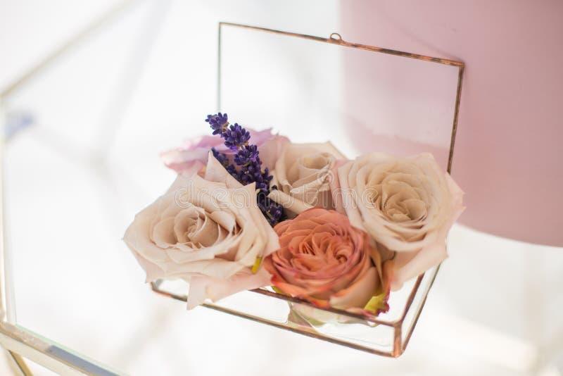 Il contenitore di vetro di primo piano per le fedi nuziali ha decorato con i fiori e il banch rosa freschi di lavanda Decorazione immagini stock