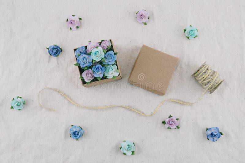 Il contenitore e la corda di regalo di Brown decorano con i fiori di carta del tono blu immagine stock libera da diritti