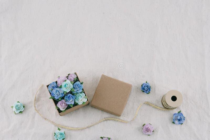 Il contenitore e la corda di regalo di Brown decorano con i fiori di carta del tono blu immagini stock