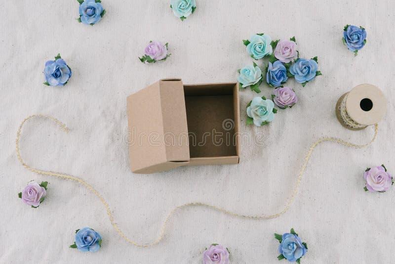 Il contenitore e la corda di regalo di Brown decorano con i fiori di carta del tono blu fotografia stock