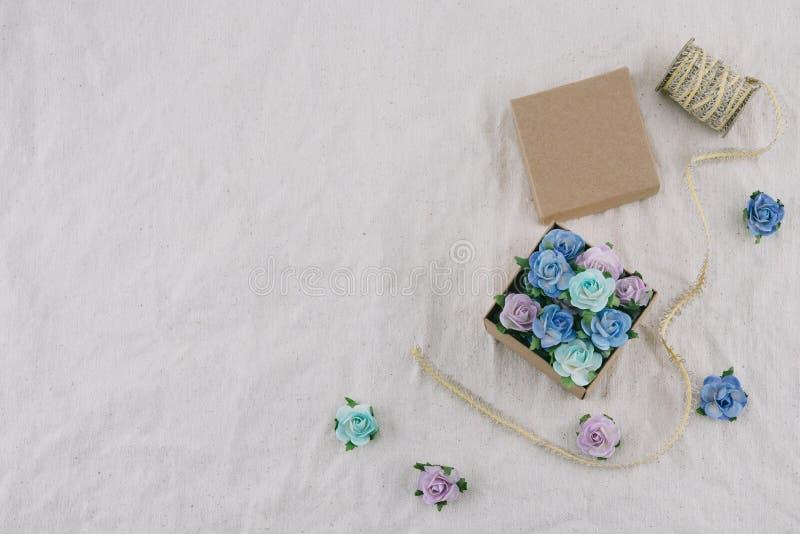 Il contenitore e la corda di regalo di Brown decorano con i fiori di carta del tono blu immagini stock libere da diritti