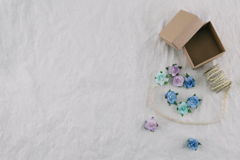 Il contenitore e la corda di regalo di Brown decorano con i fiori di carta del tono blu fotografia stock libera da diritti