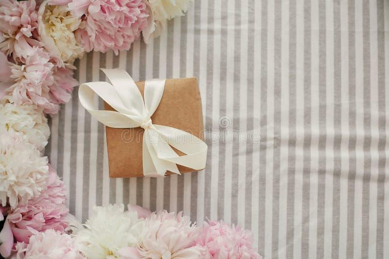 Il contenitore e le peonie di regalo del mestiere incorniciano pianamente mettono sulla tovaglia rustica Giorno di madri felice S fotografia stock libera da diritti