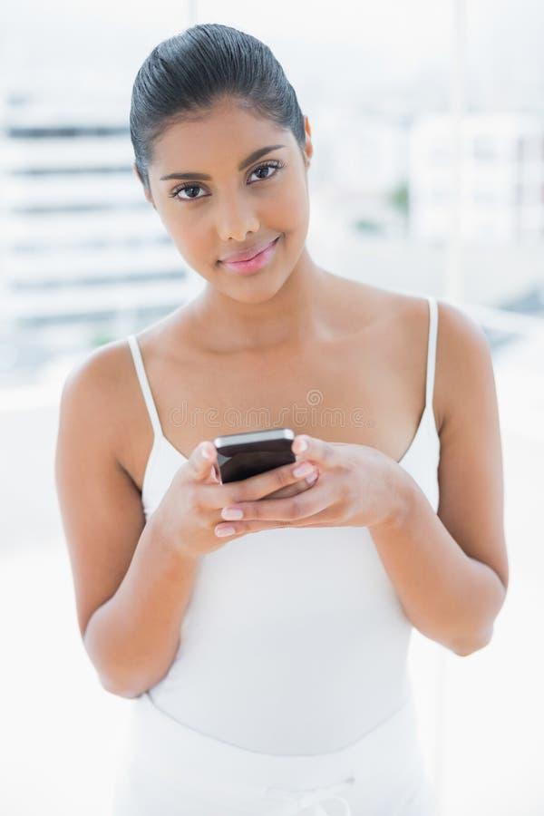 Il contenuto ha tonificato il telefono cellulare castana della tenuta immagine stock