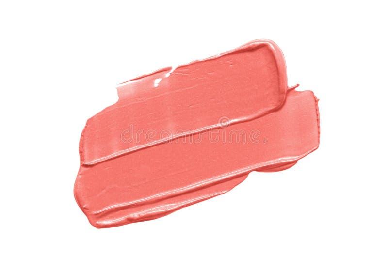 Il corallo compone il campione Colpo della macchia della sbavatura del rossetto isolato su fondo bianco immagine stock