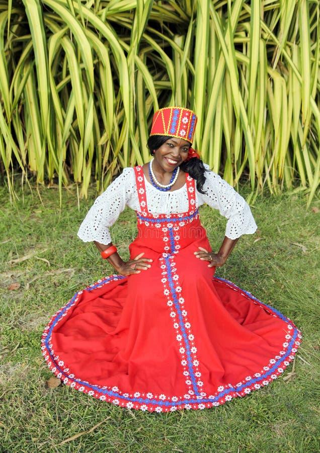 Il corpo completo verticale di una donna afroamericana allegra in un vestito russo nazionale variopinto luminoso posa nel giardin fotografia stock