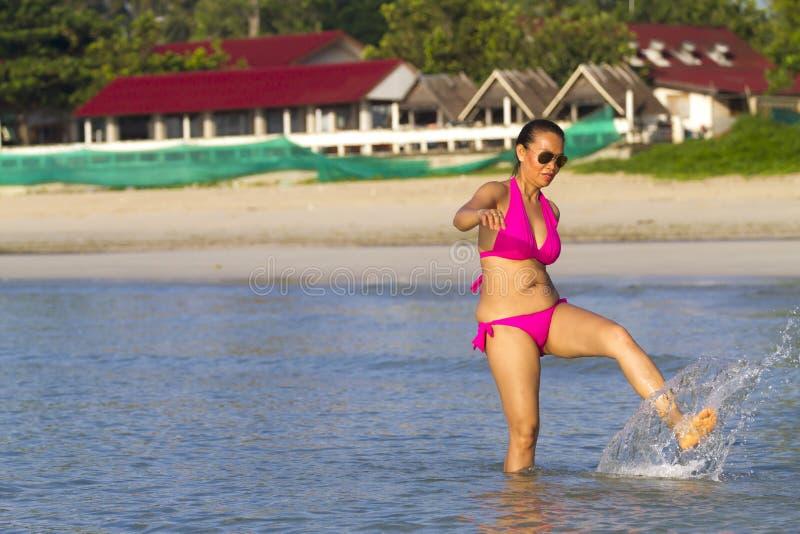 Il corpo della donna abbastanza si rilassa sulla spiaggia con il bikini rosa fotografia stock