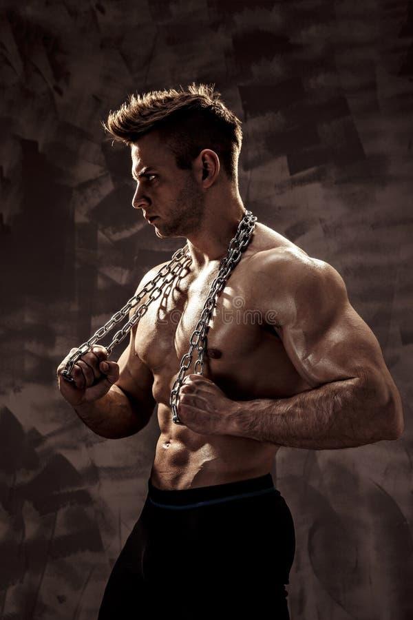 Il corpo maschio perfetto - posa impressionante del culturista Tenga una catena con il tatuaggio fotografia stock libera da diritti