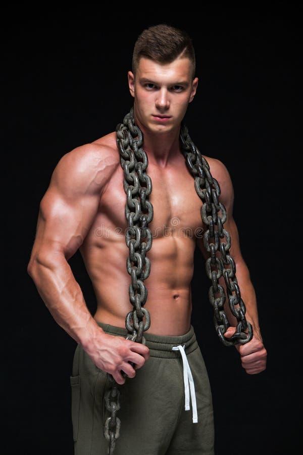 Il corpo maschio perfetto - posa impressionante del culturista Tenga una catena Isolato su priorit? bassa bianca Copi lo spazio fotografie stock libere da diritti