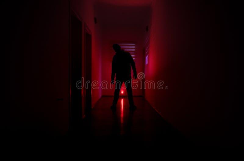 Il corridoio scuro con le porte di gabinetto e le luci con la siluetta dell'orrore spettrale equipaggiano la condizione con diffe fotografia stock