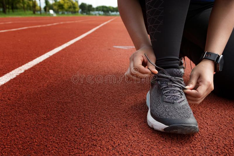Il corridore che lega le scarpe sul funzionamento segue i vicoli in stadio pronto per rac fotografie stock