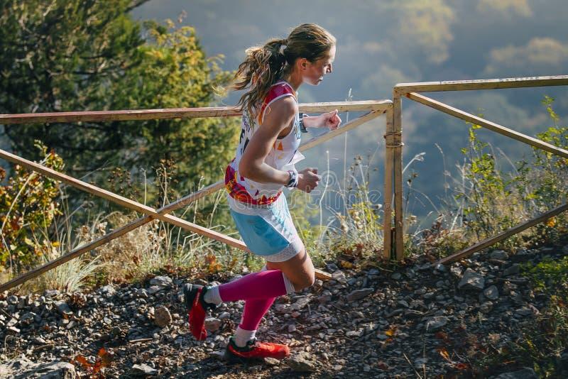 Il corridore della ragazza sta correndo su una traccia di montagna nel fondo della valle della montagna fotografia stock