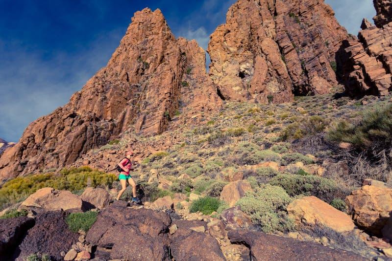 Il corridore della traccia della donna che beve in montagne d'ispirazione abbellisce fotografie stock libere da diritti