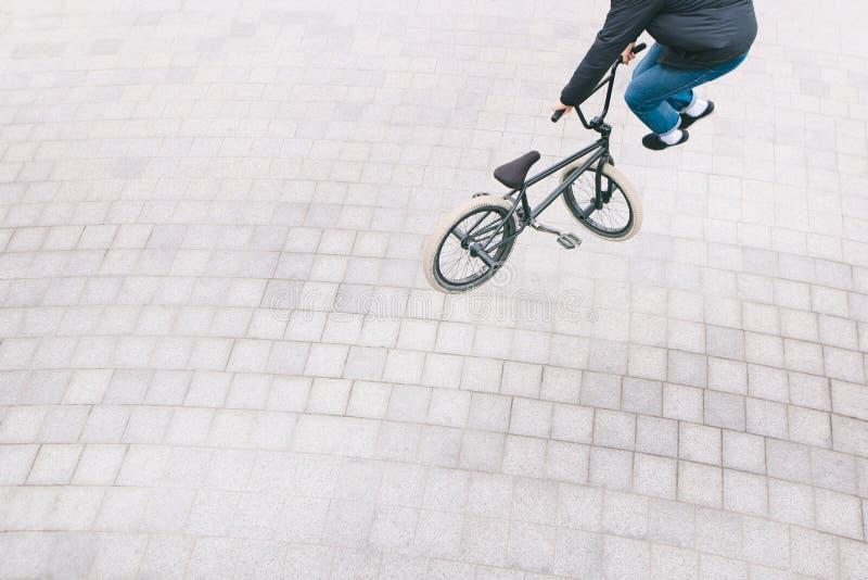 Il corridore di BMX fa i trucchi complessi Vista superiore foto minimalista di un ciclista che fa i trucchi su una bici di BMX immagini stock libere da diritti