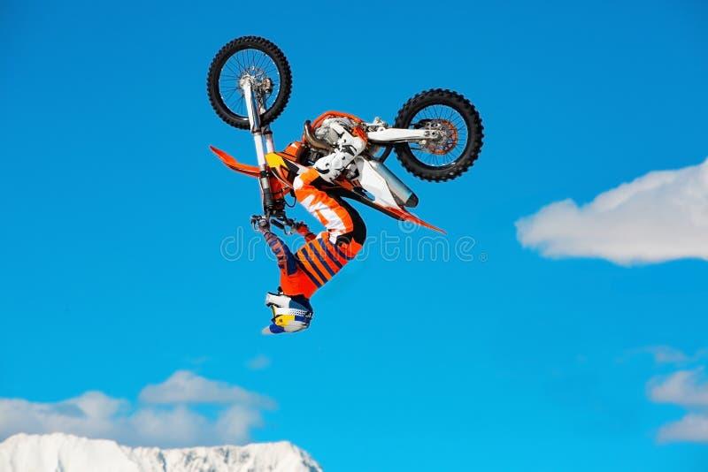 Il corridore sul motociclo partecipa alla corsa campestre di motocross in volo, salta e decolla sul trampolino contro il cielo fotografia stock libera da diritti