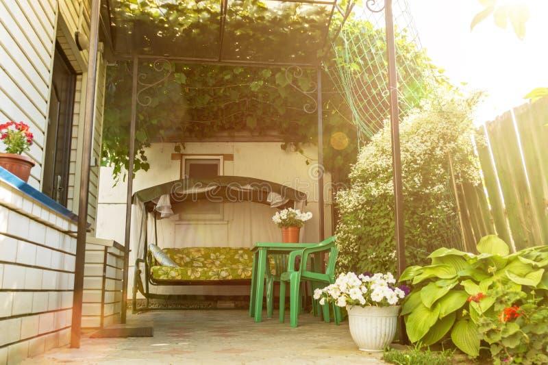 Il cortile della casetta con lo spazio di sosta sotto un baldacchino naturale dell'ombra delle viti e del sofà dell'oscillazione  immagine stock libera da diritti