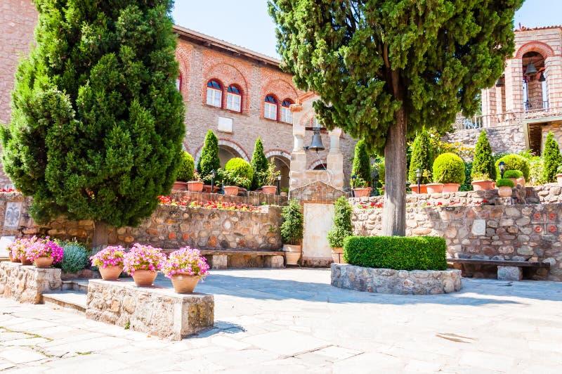 Il cortile interno di grande monastero di Meteoron o del monastero santo di grande Meteoron pieno dei fiori, piante e pini, fotografia stock libera da diritti