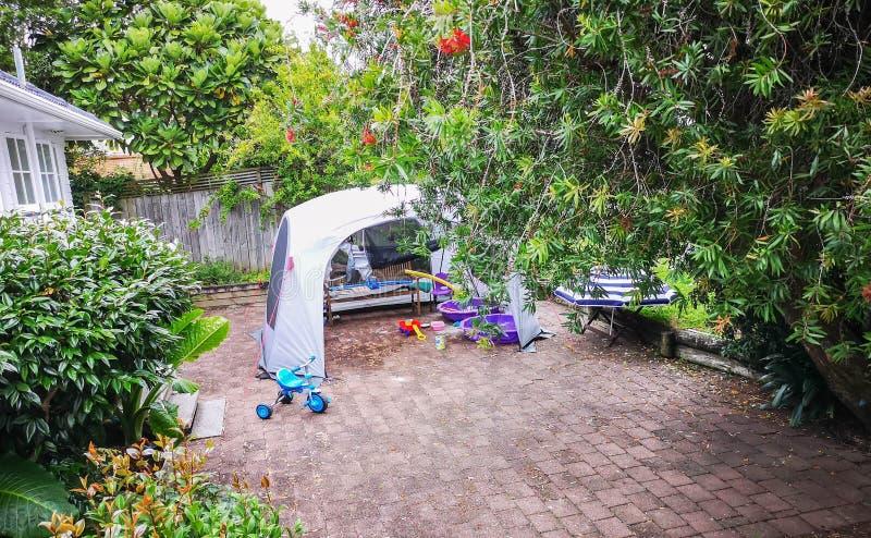 Il cortile posteriore del kiwi classico con i bambini il campo giochi ed il giardino fotografia stock libera da diritti