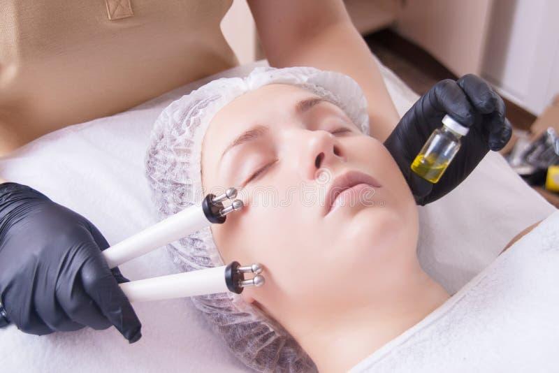 Il cosmetologo fa la procedura dell'apparato della terapia di un bello, giovane donna di Microcurrent in un salone di bellezza fotografia stock