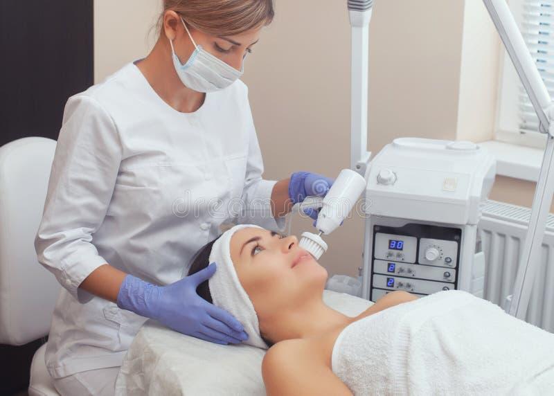 Il cosmetologo fa la procedura di pulizia del fronte dell'hardware con una spazzola girante molle di un bello, giovane donna in u fotografia stock libera da diritti