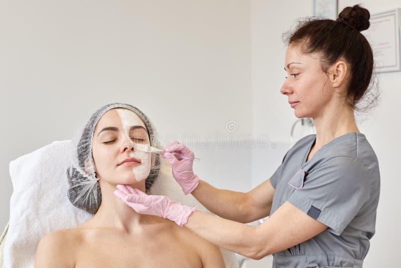 Il cosmetologo fa la procedura di pulizia e di idratazione della pelle, applicante la maschera con la spazzola speciale per affro fotografia stock