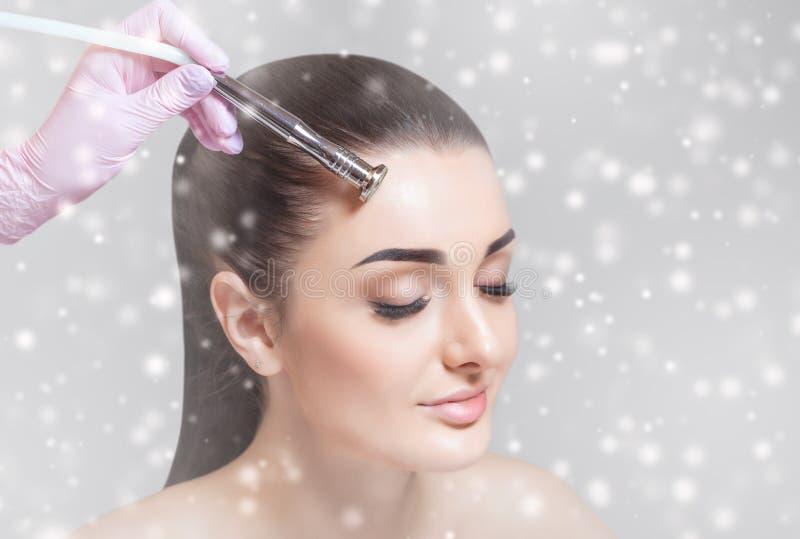 Il cosmetologo fa la procedura Microdermabrasion della pelle facciale di un bello, giovane donna in un salone di bellezza immagine stock libera da diritti