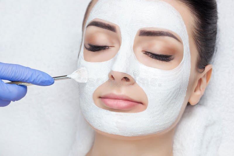 Il cosmetologo per la procedura di pulizia e di idratazione della pelle, applicante una maschera con il bastone al fronte immagine stock libera da diritti