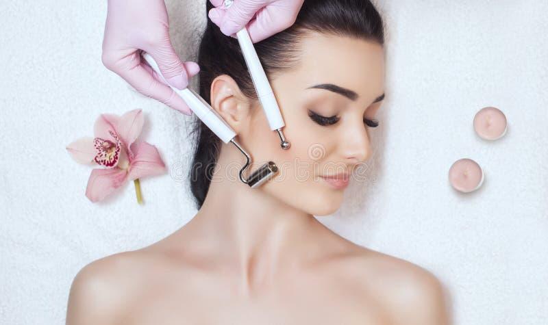 Il cosmetologo rende all'apparato una procedura della terapia di un bello, giovane donna di Microcurrent in un salone di bellezza fotografia stock
