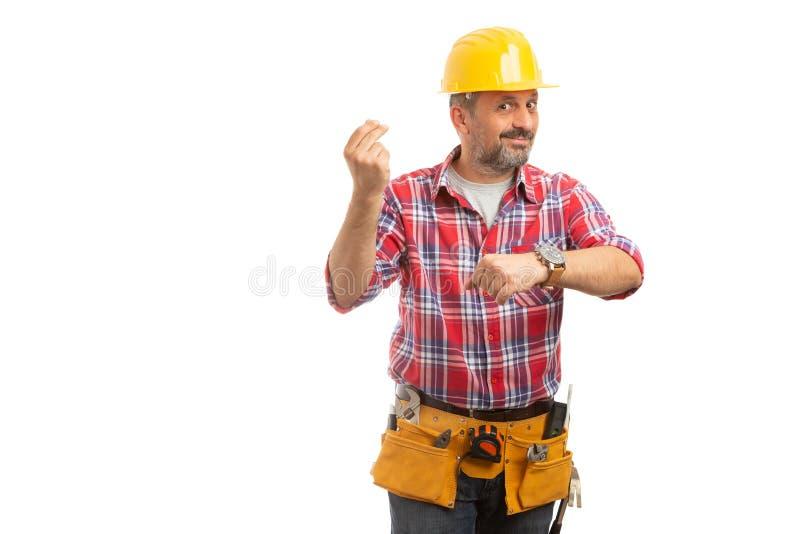 Il costruttore che fa il tempo significa il gesto dei soldi immagine stock