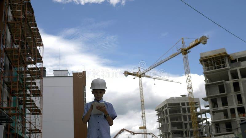 Il costruttore che il ragazzo sta fra le gru del costruttore facendo uso della compressa, ragazzo gioca un costruttore fotografie stock